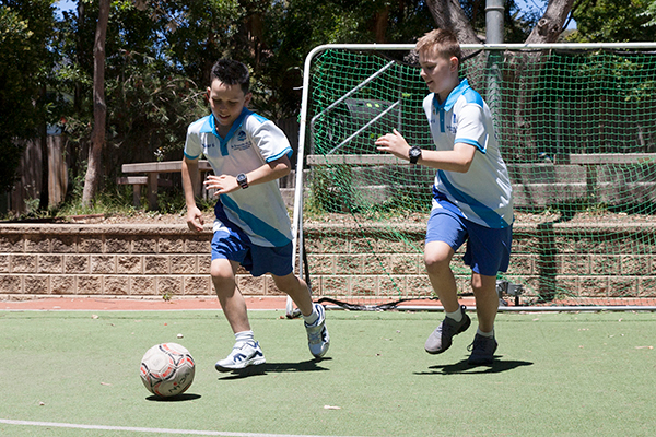 St Francis de Sales Catholic Primary School Woolooware Co-curricular Sport Two students racing towards soccer ball