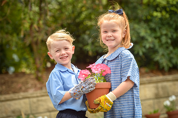 St Francis de Sales Catholic Primary School Woolooware Student Wellbeing Two students holding a flower pot and smiling